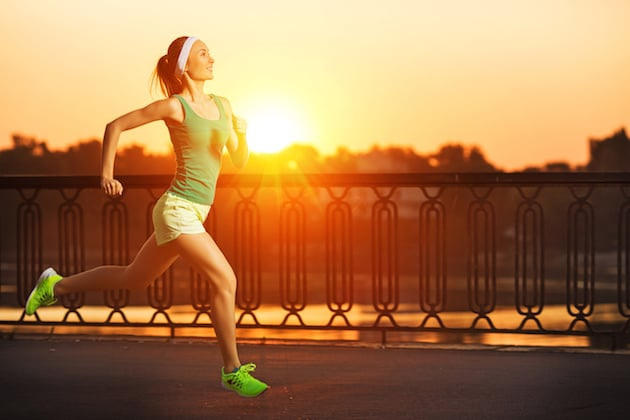 Running woman. Runner is jogging in sunny bright light on sunrise. Female fitness model training outside in the city on a quay.